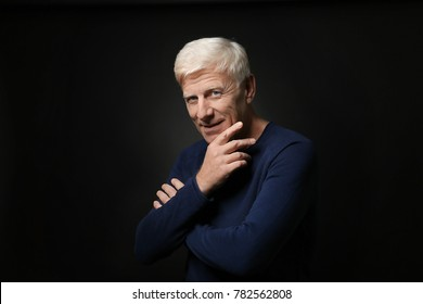 Portrait of handsome mature man on dark background
