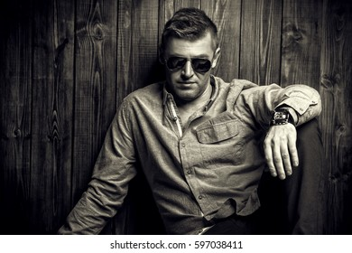 Portrait of a handsome mature man in sunglasses over wooden wall background. Men's beauty, fashion.