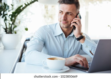 Portrait of a handsome mature man talking on mobile phone and using laptop computer while sitting at the cafe table indoors