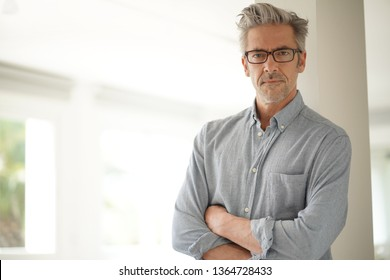 Portrait of handsome mature man wearing glasses smiling at camera