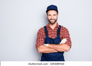 Portrait of handsome mechanic with stubble in blue overall, shirt having his arms crossed, looking at camera, isolated on grey background