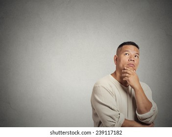 Portrait handsome middle aged man thinking looking up isolated grey wall background with copy space. Human face expressions, emotions, feelings, body language, perception