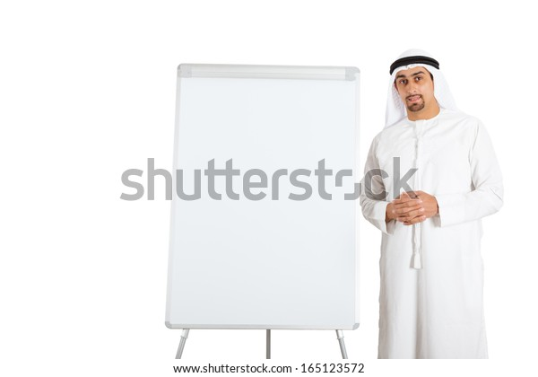 Portrait of a handsome Middle Eastern businessman standing next to presentation board.