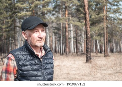 Portrait of a handsome middle-aged man in a cap. Adult man in shirt and vest outdoors in the park. Copy space.