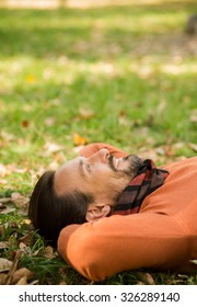 Portrait of handsome middle-aged man lying on the autumn leaves in the park. Happy man enjoing beautiful nature and environment.