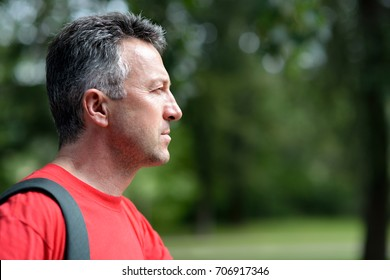 Portrait of handsome middle-aged man in profile in summer park.