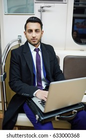 Portrait of handsome Middle-Eastern businessman in subway train, working with laptop and looking at camera