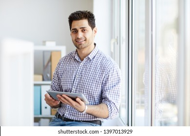 Portrait of handsome Middle-Eastern man looking at camera while posing by window holding tablet, copy space