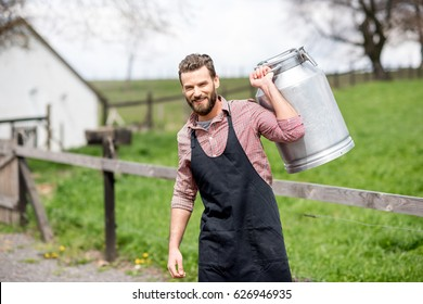 Portrait of a handsome milkman in apron walking with milk container outdoors on the rural scene background