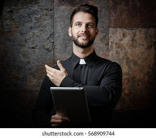 Portrait of handsome modern young catholic priest preaching from tablet.
