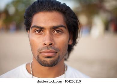 Portrait of handsome multi-ethnic man on beach at sunset