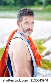portrait of handsome muscular athlete standing outdoors with towel on his shoulder