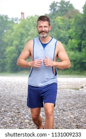 portrait of handsome muscular bearded athlete running outdoors
