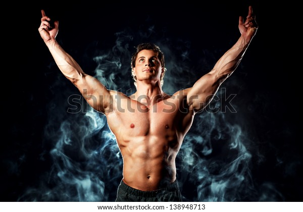 Portrait of a handsome muscular bodybuilder posing over black background.