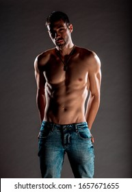 Portrait of a handsome muscular man posing against black background