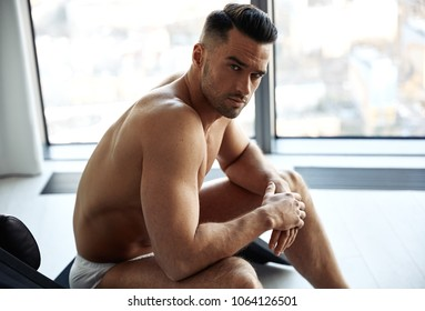 Portrait of a handsome, muscular man relaxing in a luxurious apartment