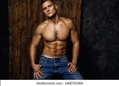 Portrait of handsome muscular and sexy man wearing jeans is posing against wooden background
