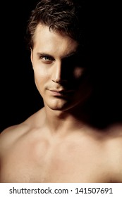 Portrait of a handsome muscular young man. Black background.