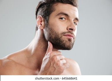 Portrait of a handsome naked bearded man examining his face isolated over white background