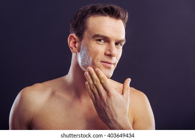 Portrait of handsome naked man applying cream on his face, looking at camera and smiling, on a dark background