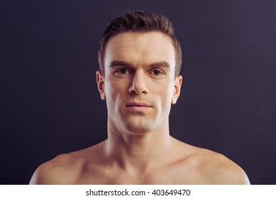 Portrait of handsome naked man looking at camera, on a dark background