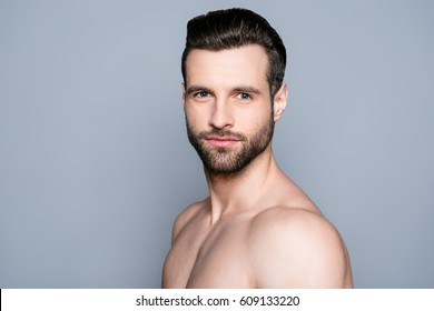 A portrait of a handsome naked man on gray background is going to have a shower.