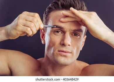 Portrait of handsome naked man plucking his eyebrows, on a dark background, close up