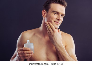 Portrait of handsome naked man smiling, holding aftershave lotion and applying it, on a dark background
