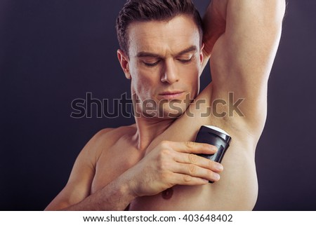 Portrait of handsome naked man using an antiperspirant, on a dark background