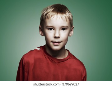 portrait of a handsome nine year old boy against green background
