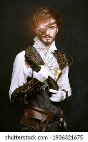 Portrait of a handsome noble man with steampunk gadgets and a gun on a black background. Steampunk concept.