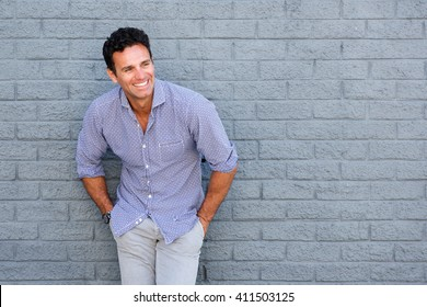 Portrait of a handsome older man laughing against gray background