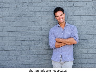 Portrait of a handsome older man smiling with arms crossed against gray background