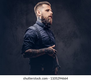 Portrait of a handsome old-fashioned hipster in a blue shirt and suspenders, posing in a studio.