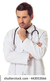Portrait of handsome pensive doctor in white coat keeping hand on his chin and thinking, isolated on white background