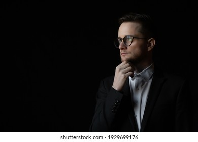Portrait of a handsome pensive young bearded businessman wearing suit and eyeglasses standing isolated over black background with copy space.