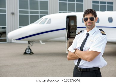 Portrait of handsome pilot with arms crossed standing in front of private jet