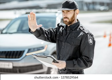 Portrait of a handsome policeman in uniform standing in front of a car on the roadside