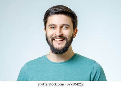 Portrait of handsome positive young man isolated on gray background