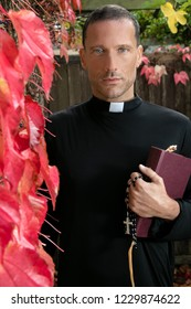 Portrait of handsome priest holding his bible and looking at camera while standing in garden