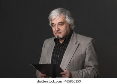 Portrait of handsome professor man in business suit holding clipboard. Demanding teacher of university or college looking at camera in studio.