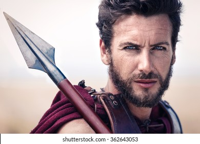 Portrait of handsome and proud ancient warrior in armor with spear. Spartan Soldier. Landscape background