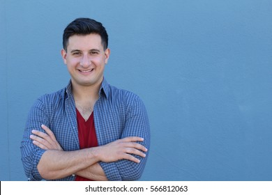 Portrait of handsome real looking man smiling with his arms crossed