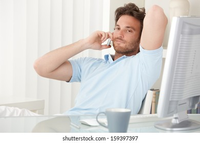 Portrait of handsome relaxed man sitting at desk making phone call on mobile, smiling.
