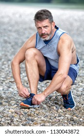 portrait of handsome runner in his 40s tying his shoes