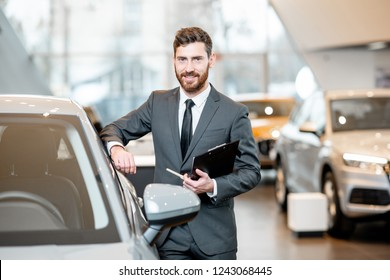 Portrait of a handsome salesman in the suit standing near the car in the showroom
