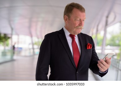 Portrait of handsome senior businessman with mustache exploring the city of Bangkok, Thailand