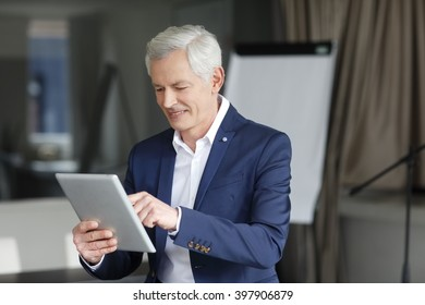 Portrait of a handsome senior businessman working on his digital tablet while sitting at office.