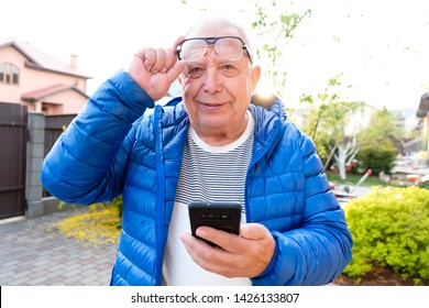 Portrait of handsome senior man 70-75 years old using smartphone outdoors. Older man read sms with phone. Lifestyle, technology concept. Happy grandfather