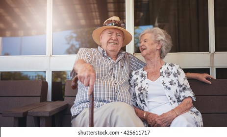 Portrait of handsome senior man sitting with his wife on a bench outside their house. Retired couple taking a break and relaxing outside their home.